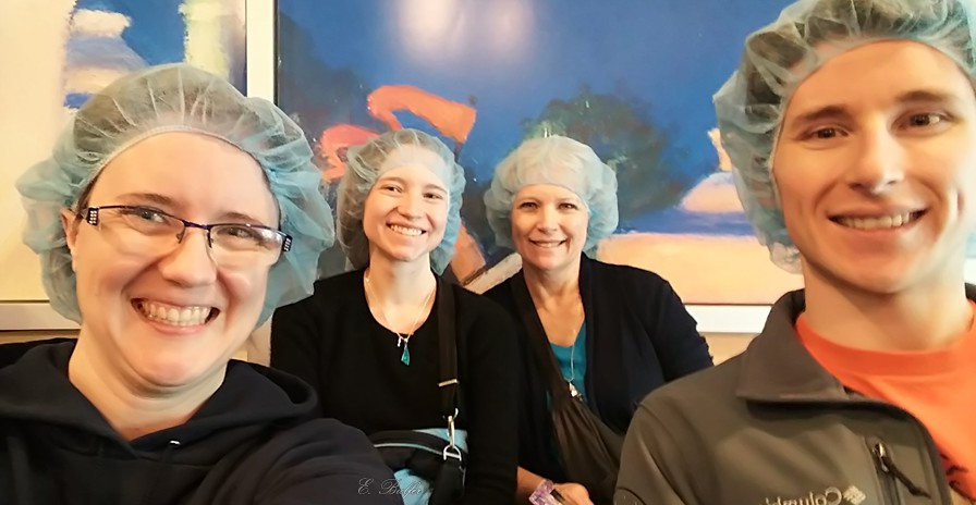 Four smiling people wearing hairnets.
