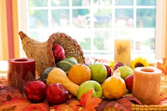Cornucopia spilling winter squashes and apples onto a table with fall leaves on it, and three unlit pillar candles around the centerpiece.