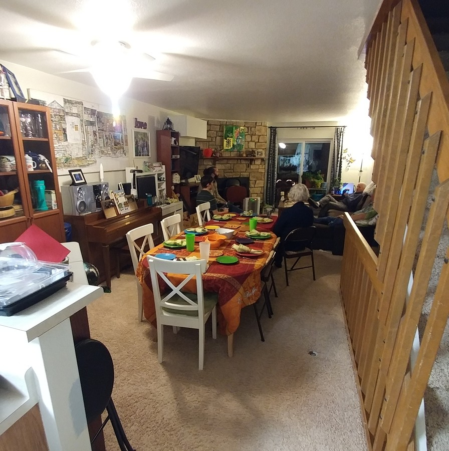 Wide-angle photo of a table set for ten in a very narrow space.