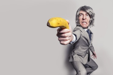 "Gray haired man in a gray suit holding a banana as if it was a gun and making a ""grr"" face."