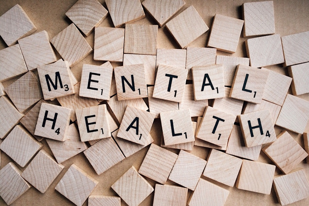 "Blank wooden scrabble tiles with ""Mental Health"" spelled out in tiles laid on top."