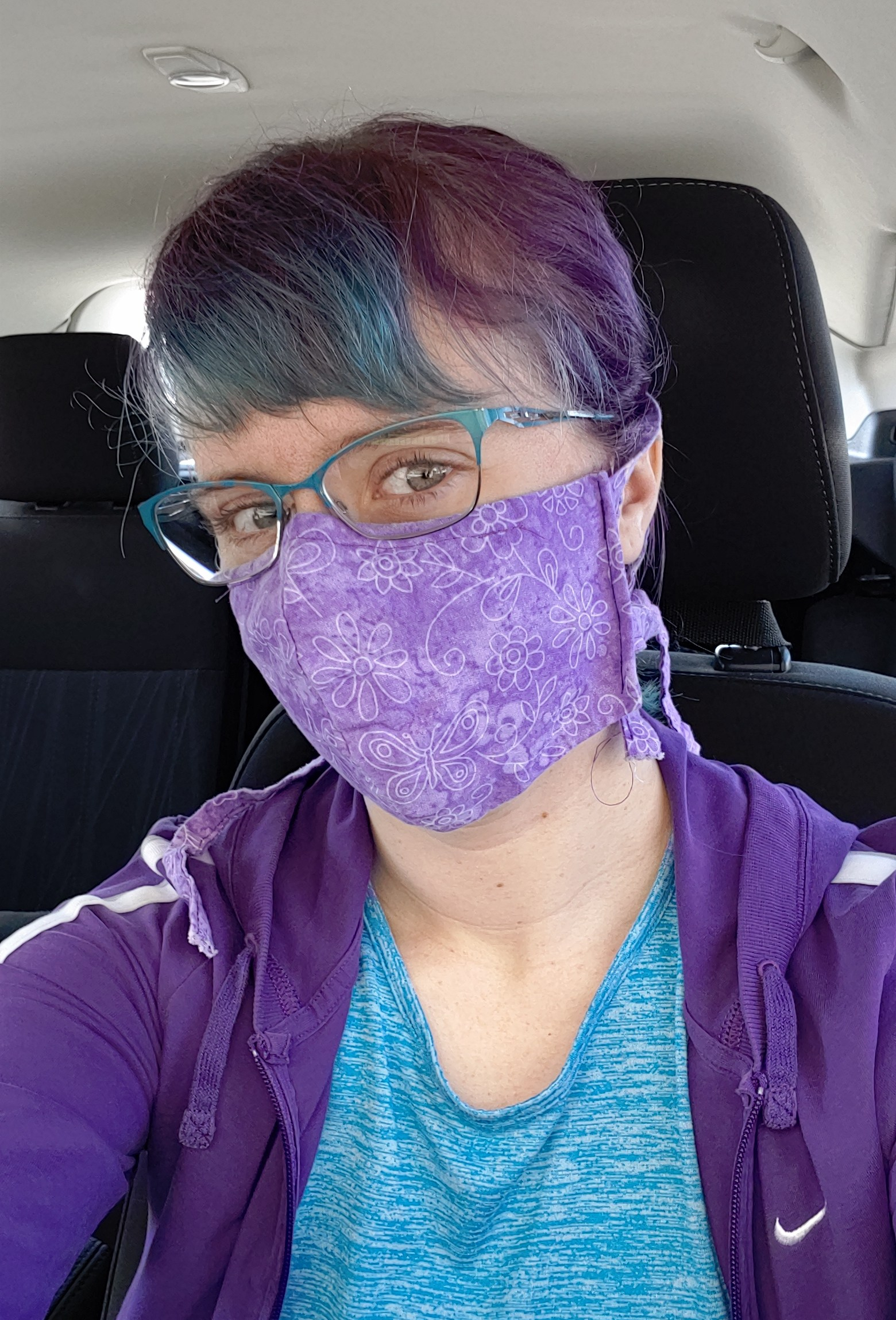 White woman with purple and blue hair, wearing blue glasses, a purple face mask, blue shirt, and purple jacket, sitting in a car with black seats.