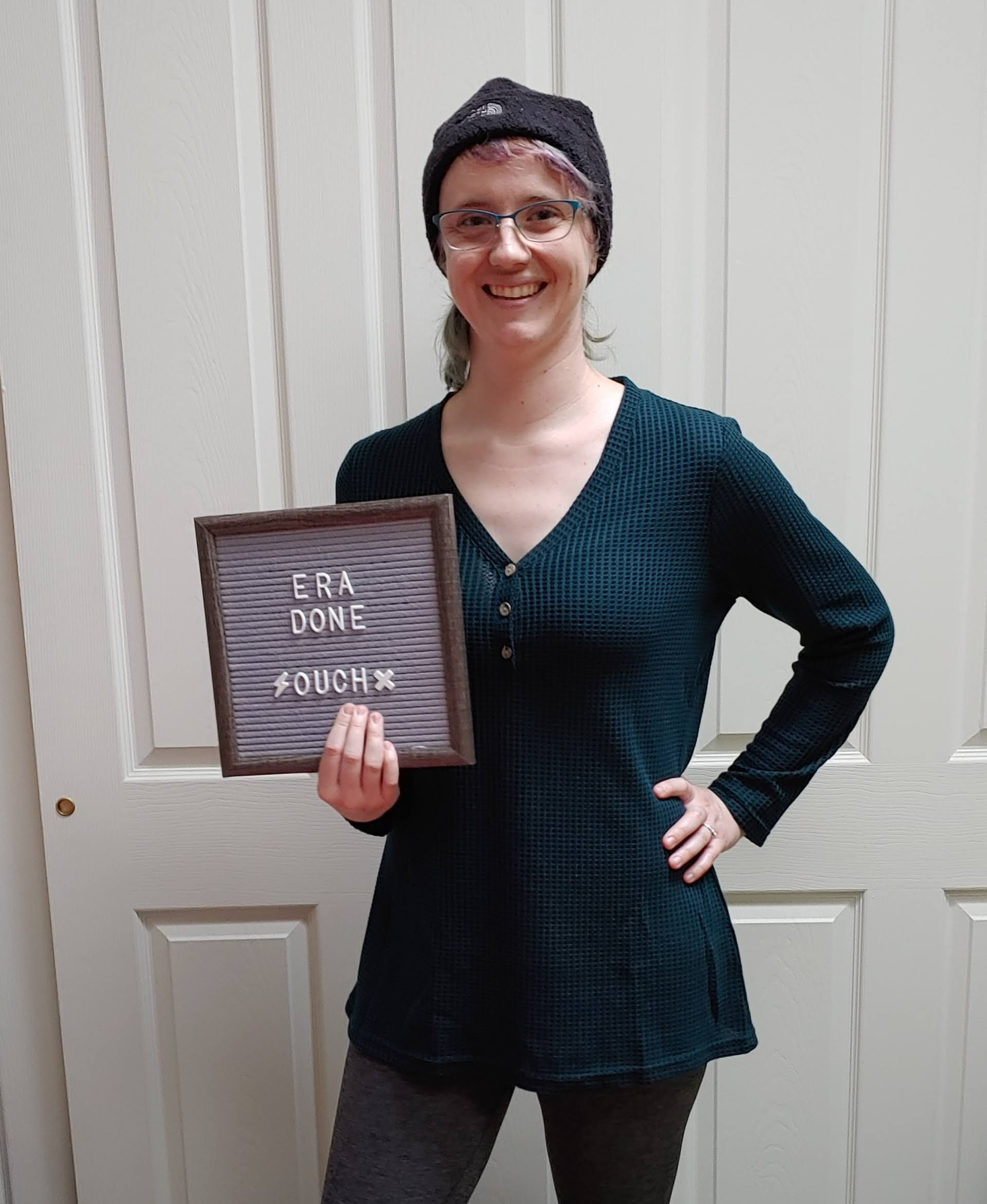 "White woman in a dark green long sleeve shirt and black beanie. She's holding a gray letter board that has ""era done, ouch"" on it in white letters."