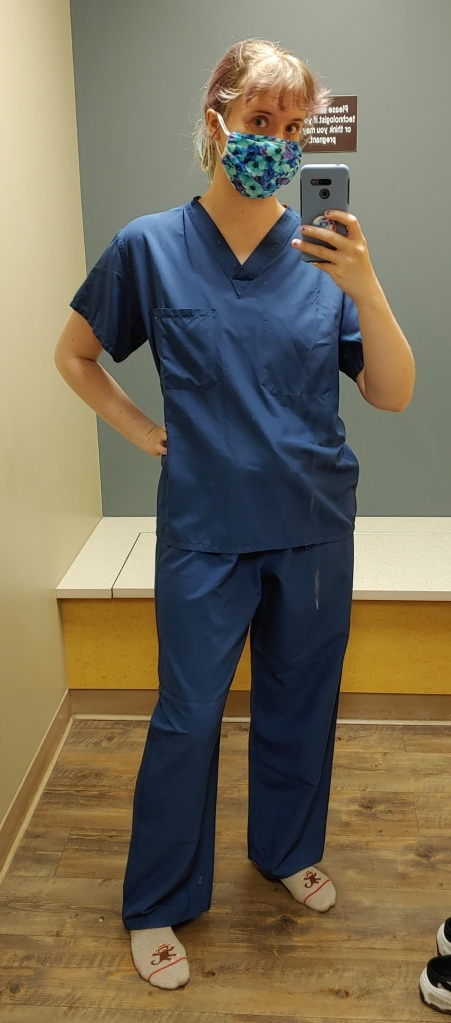 White woman in a blue floral face mask, and navy blue scrubs, posing for a mirror selfie.